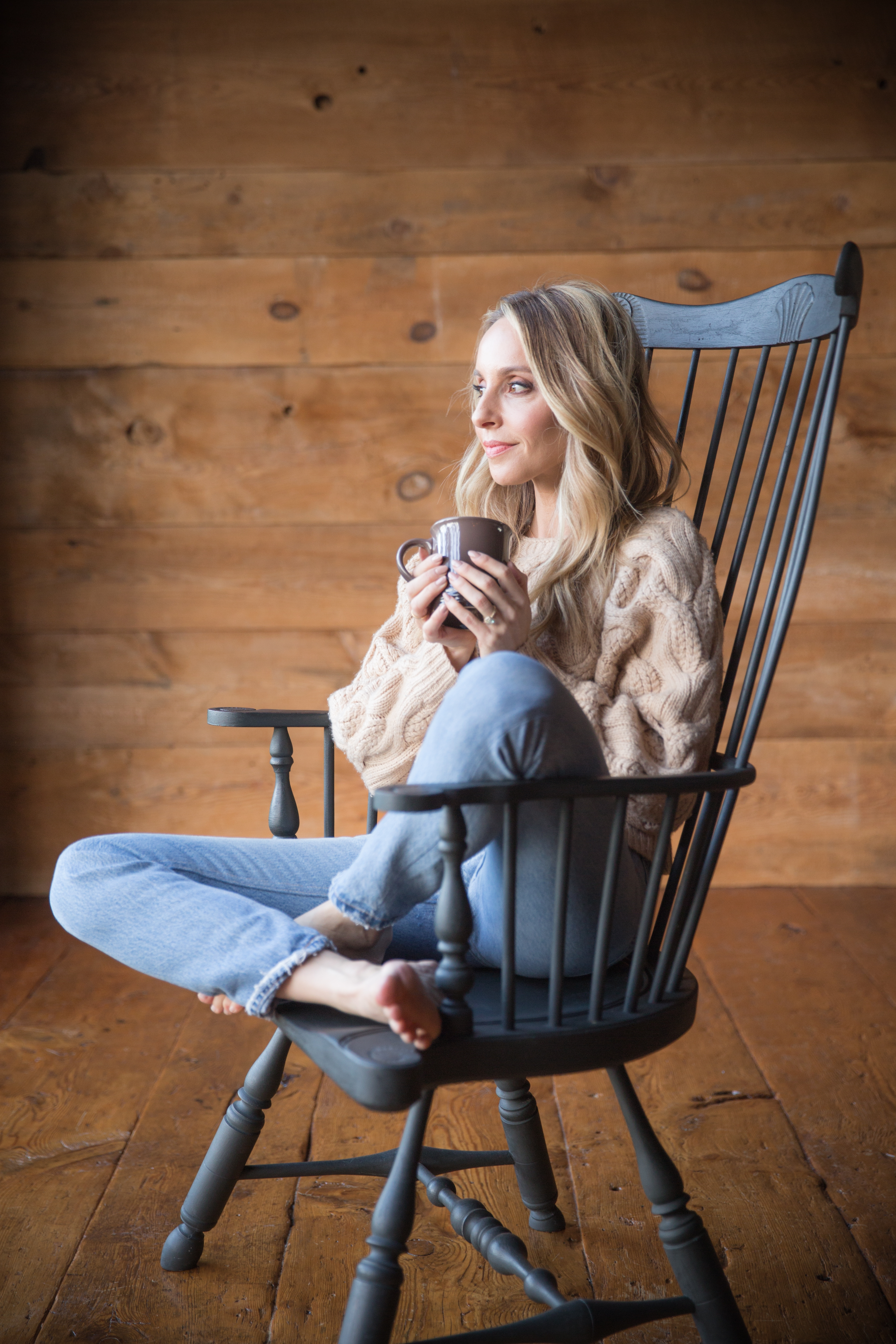 gabby bernstein relaxing in a wooden chair with a mug of tea