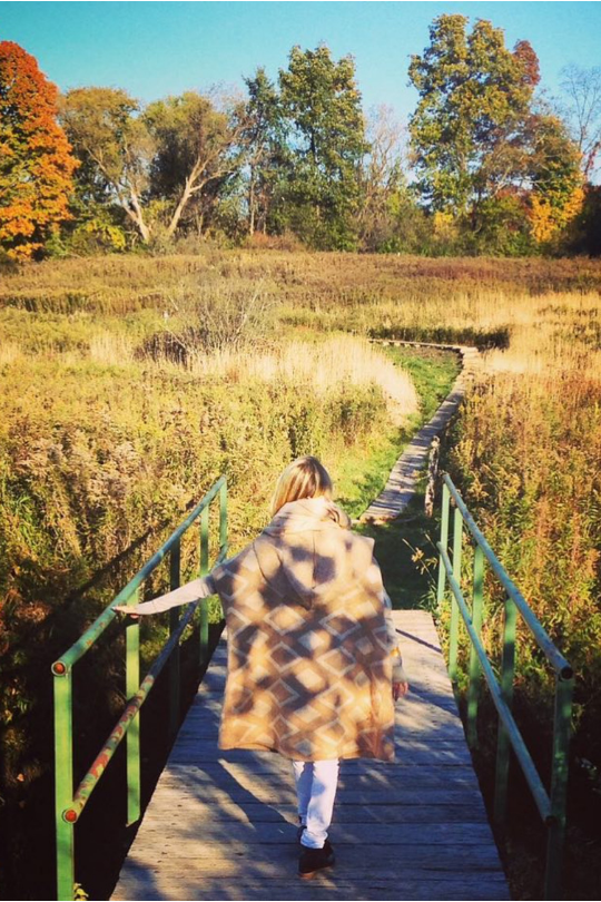 Gabby Bernstein walking in a field in autumn