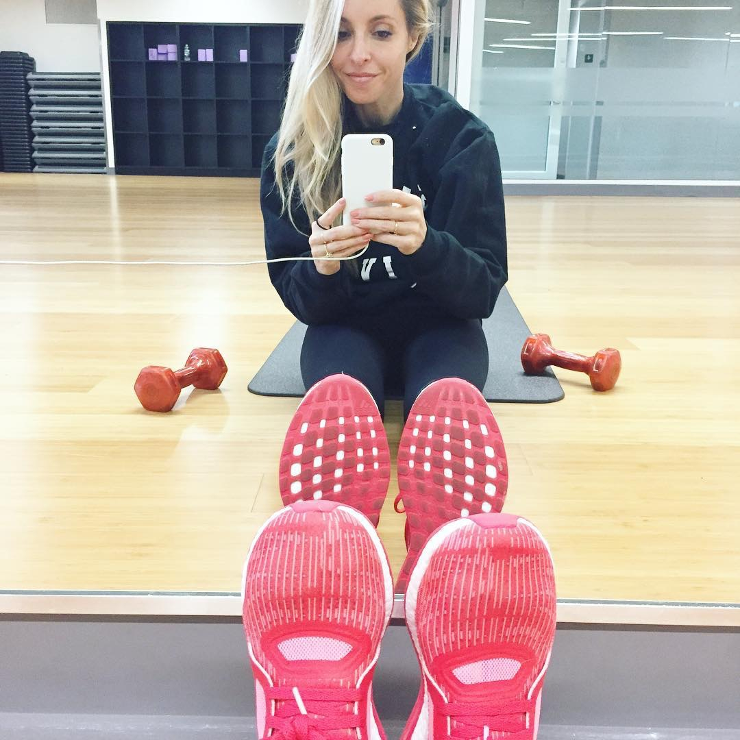 Gabby Bernstein sitting on the edge of a yoga mat in the gym, wearing red sneakers | Start the new year
