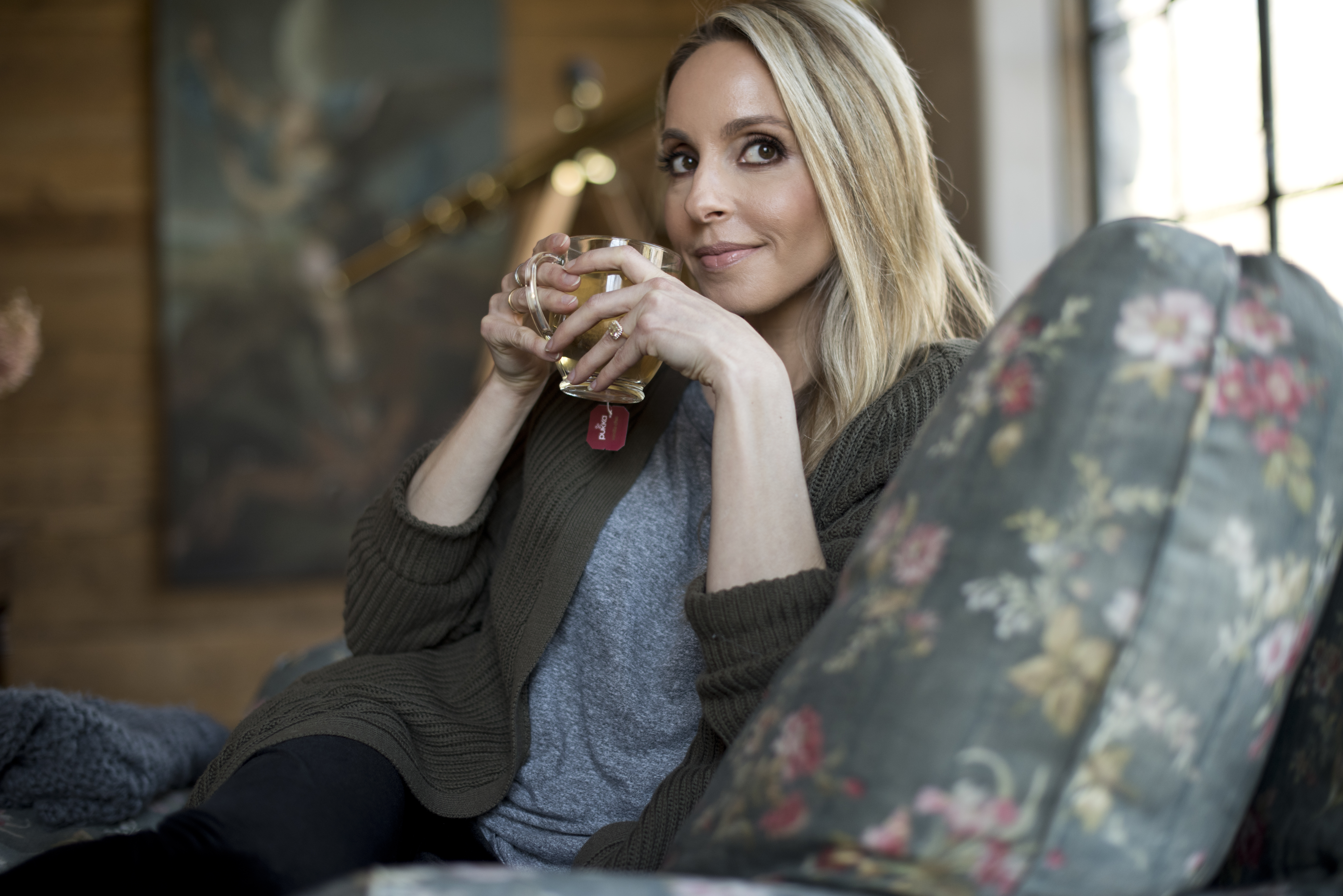 gabby bernstein cozy in a chair with mug of tea