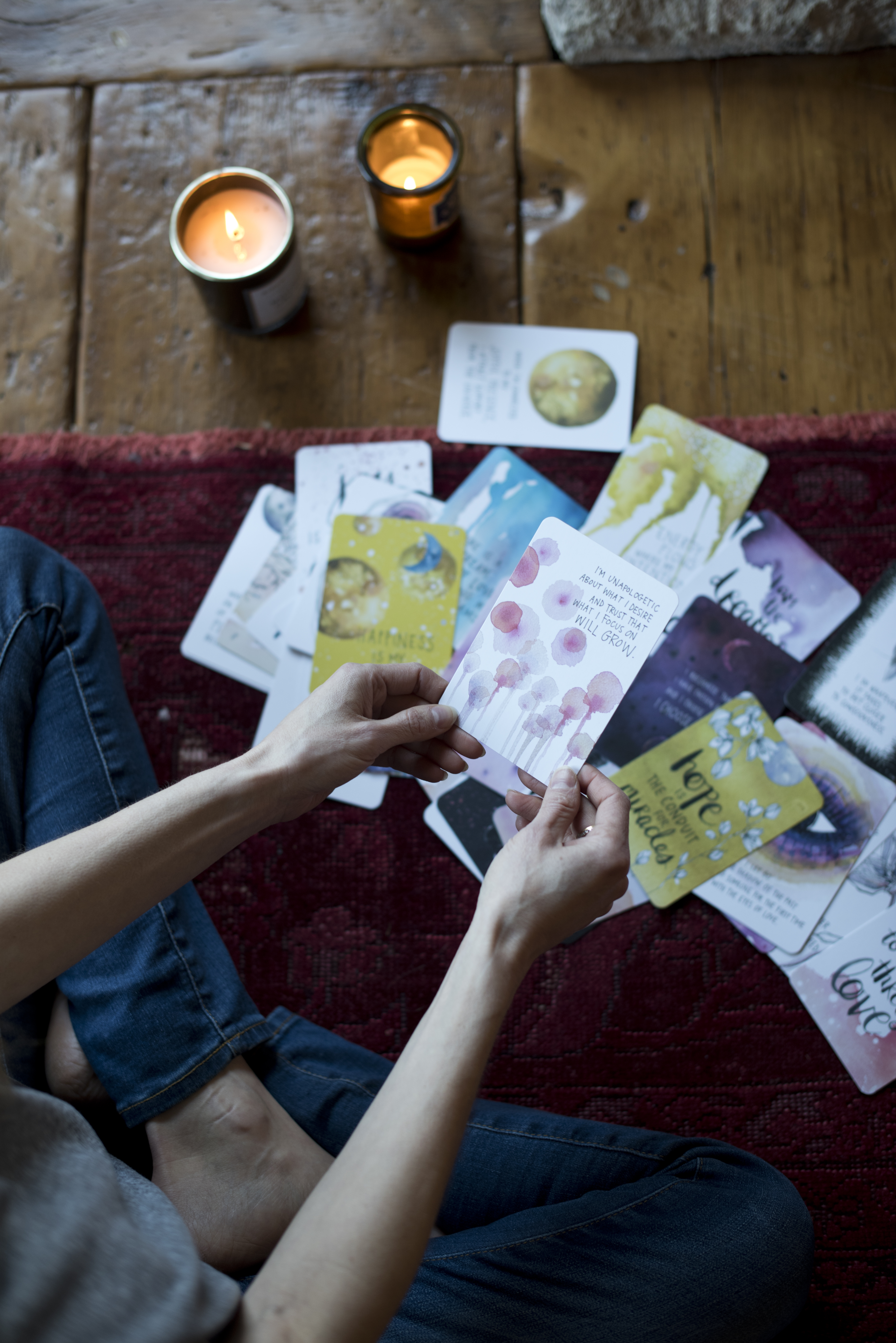 gabby bernstein in her meditation space with candles and 'the universe has your back' card deck